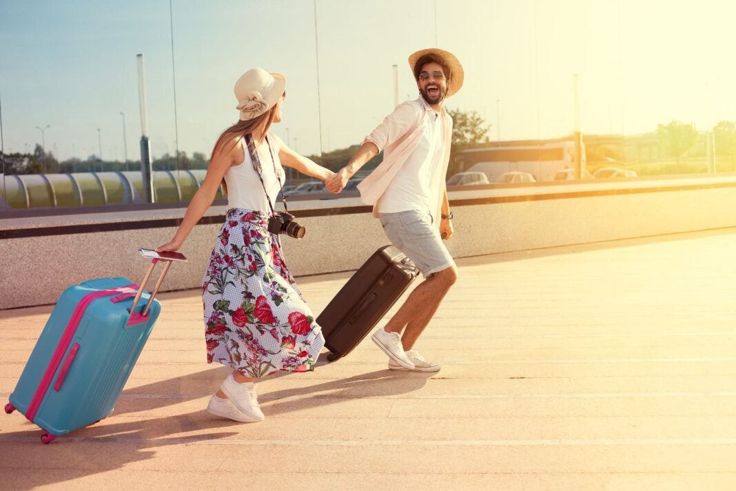 A couple with suitcases running and holding hands