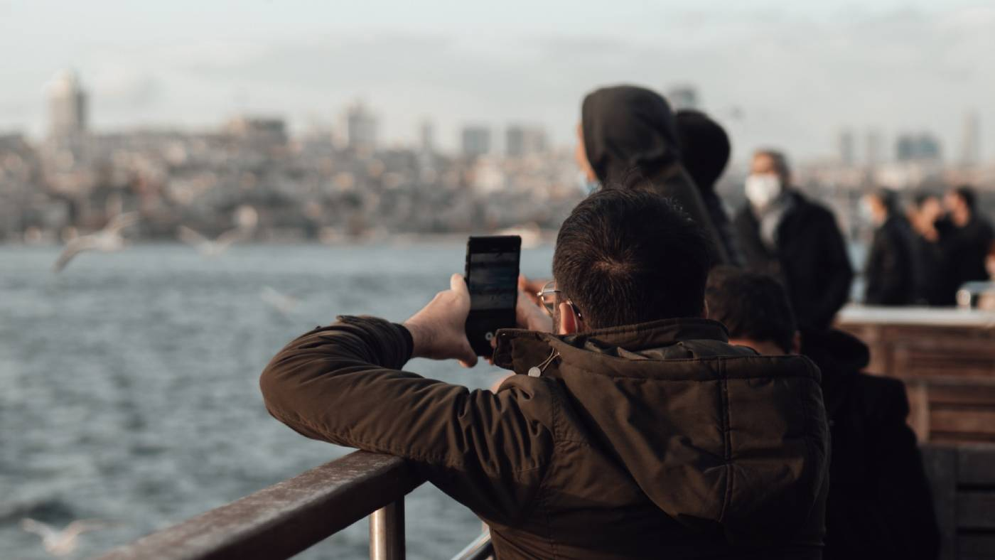 Person filming city and ocean with smartphone